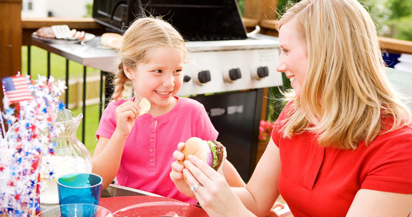 Picture shows an adult and child enjoying a sandwich and celebrating 4th of July.