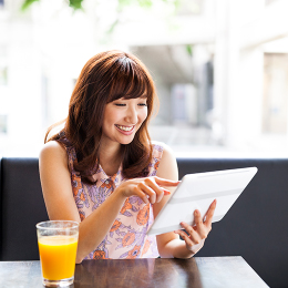 Woman using tablet in restaurant.