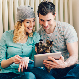 Young couple and dog using tablet.