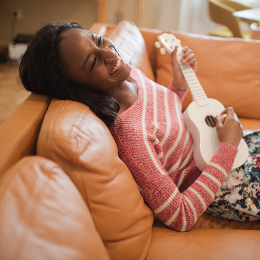 Woman sitting on couch playing guitar.